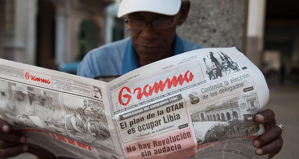 Cubano leyendo el diario oficial Granma...